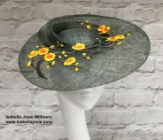 Dark Green Swirl Ascot Hat with Yellow Blossom Trim by Isabella Josie Millinery